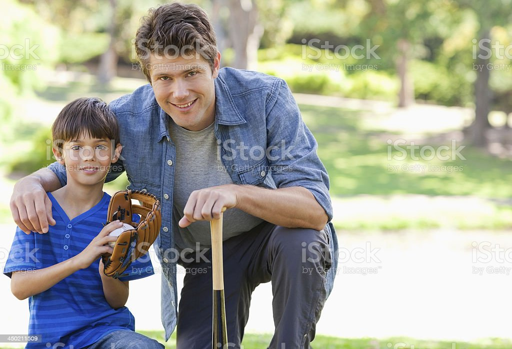 Dad and his son getting ready to play baseball stock photo