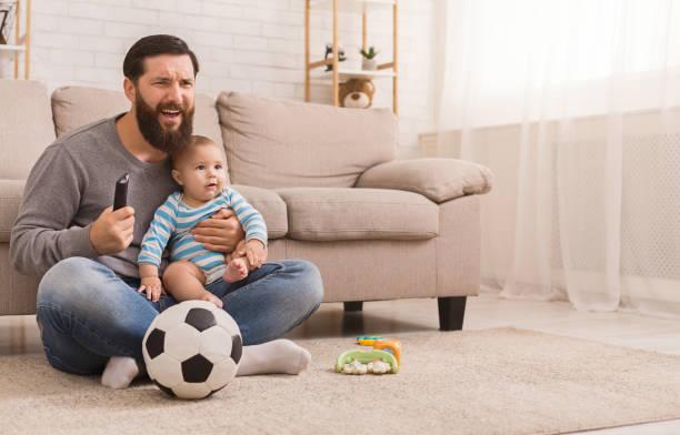 papa et son fils regardant le football à la maison - chrono sport photos et images de collection