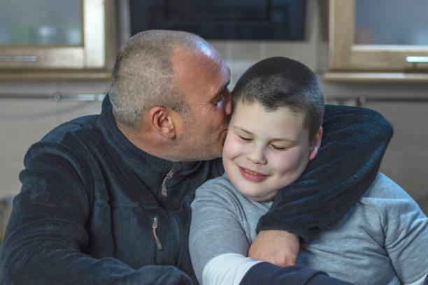 vater und sein sohn mit autismus sitzen in der küche zu hause. ein mann mit kurzen haaren und borste umarmt seinen sohn und küsst ihn auf die wange. - genderblend stock-fotos und bilder