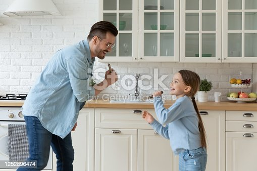 Overjoyed dad little daughter singing dancing in kitchen holding hand beater and fork like microphones, pretend like superstar enjoy weekend activity together at home, having fun before cook concept