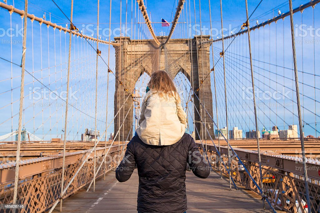 Dad and little girl on Brooklyn bridge, New York City Brooklyn Bridge over East River viewed from New York City, USA 2015 Stock Photo