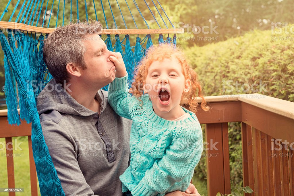 Dad and little redhead girl goofing around in a hammock. stock photo