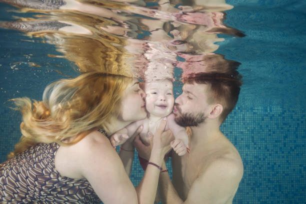 Dad and mom kiss a little boy underwater in the pool. Healthy family lifestyle and children water sports activity. Child development, disease prevention stock photo
