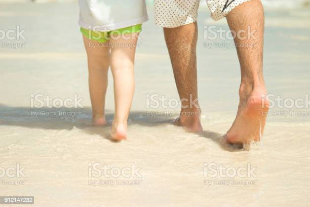 Dad and son are walking along the beach closeup of legs picture id912147232?b=1&k=6&m=912147232&s=612x612&h=m5deln atulbywt0myop24wdivyudpbzulphkxx2dyi=