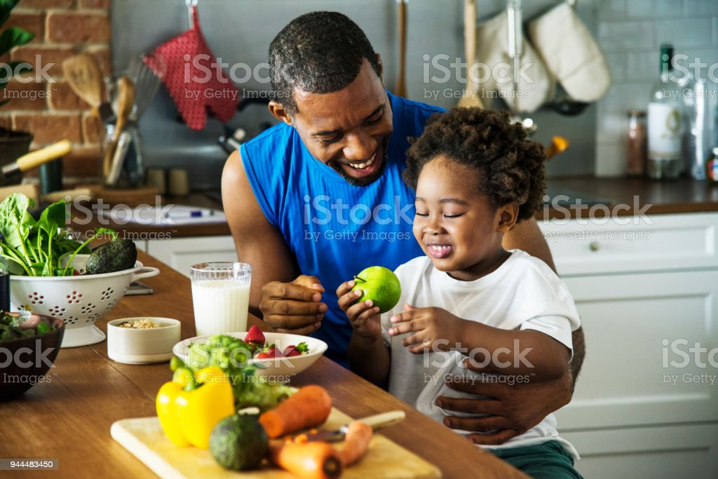 Dad and son cooking together stock photo