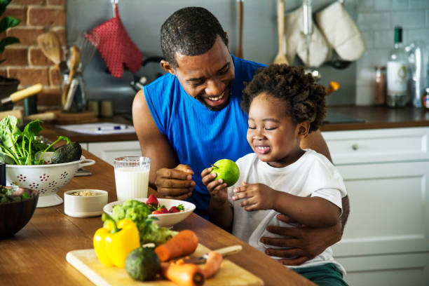 dad and son cooking together - family health stock photos and pictures