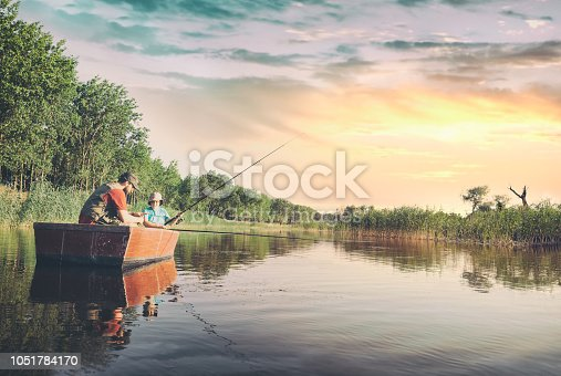 Dad and son sitting in boat and fishing on lake, the boy showing his dad how he caught a fish