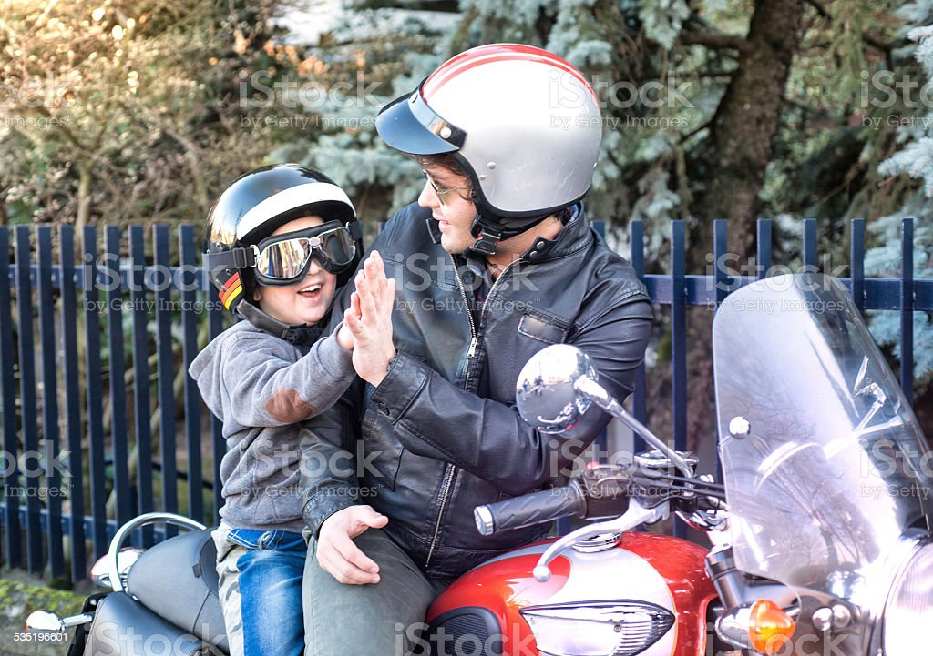 Dad and Son Giving a Five Riding a Motorcycle stock photo