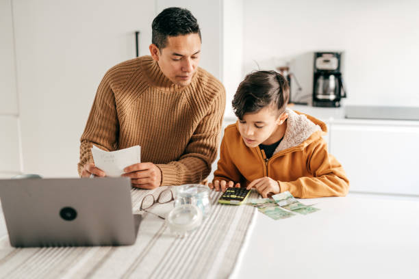 Dad and son - homeschooling from home office stock photo