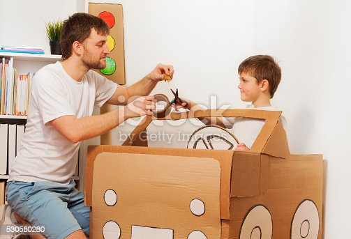 942256562istockphoto Dad and son making big toy cardboard car at home 530580280