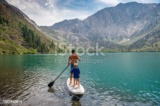 Dad and Son Paddle Boarding on a mountain lake.