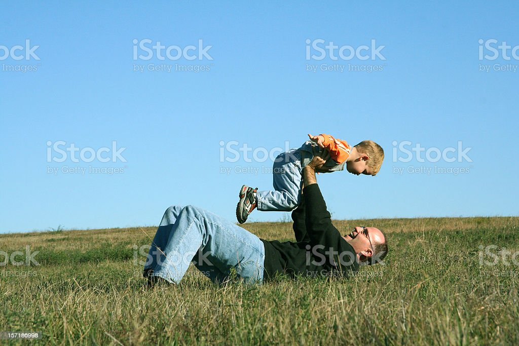 Dad and Son playing Airplane in Field royalty-free stock photo