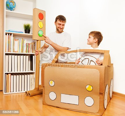 942256562istockphoto Dad and son playing drivers with cardboard car 530581086