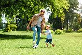 dad and son playing football at park