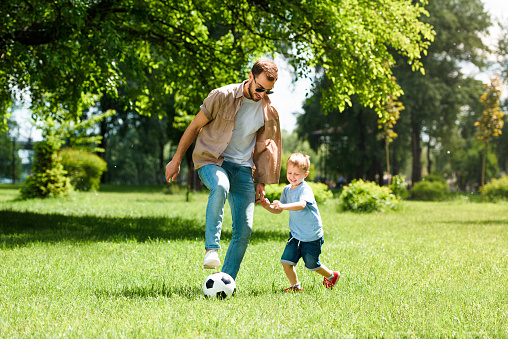 Dad And Son Playing Football At Park — стоковые фотографии и другие картинки Атлетизм