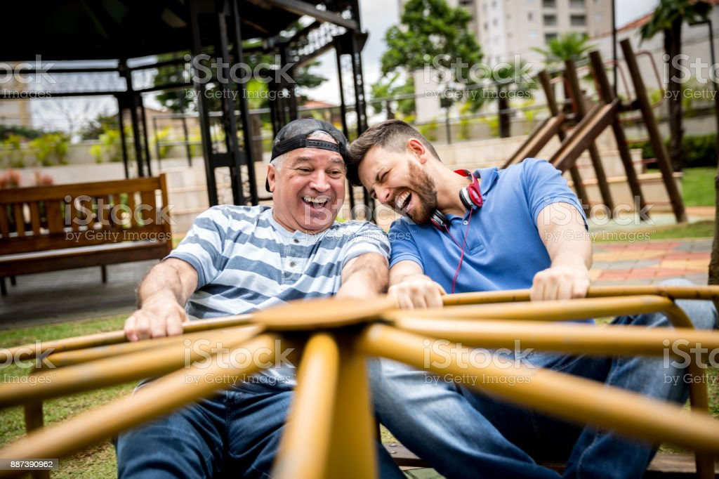 Dad and son playing on roundabout stock photo
