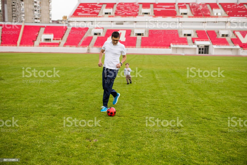 Dad and son playing soccer royalty-free stock photo