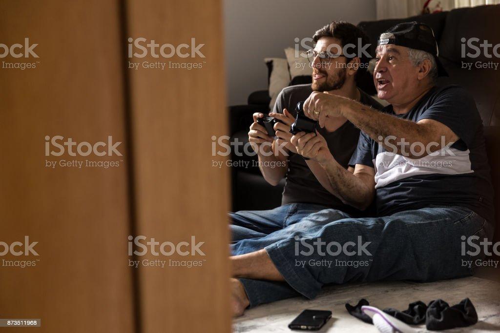 Pai e filho jogando vídeo game em casa - foto de acervo