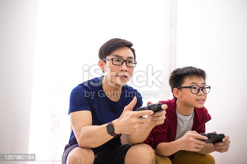 Dad and son playing video game happily
