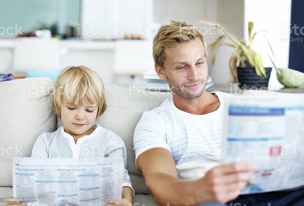 Dad and son reading newspapers together on couch. stock photo