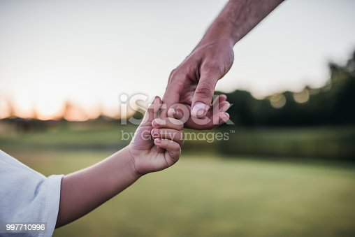 istock Dad and son taking hands 997710996