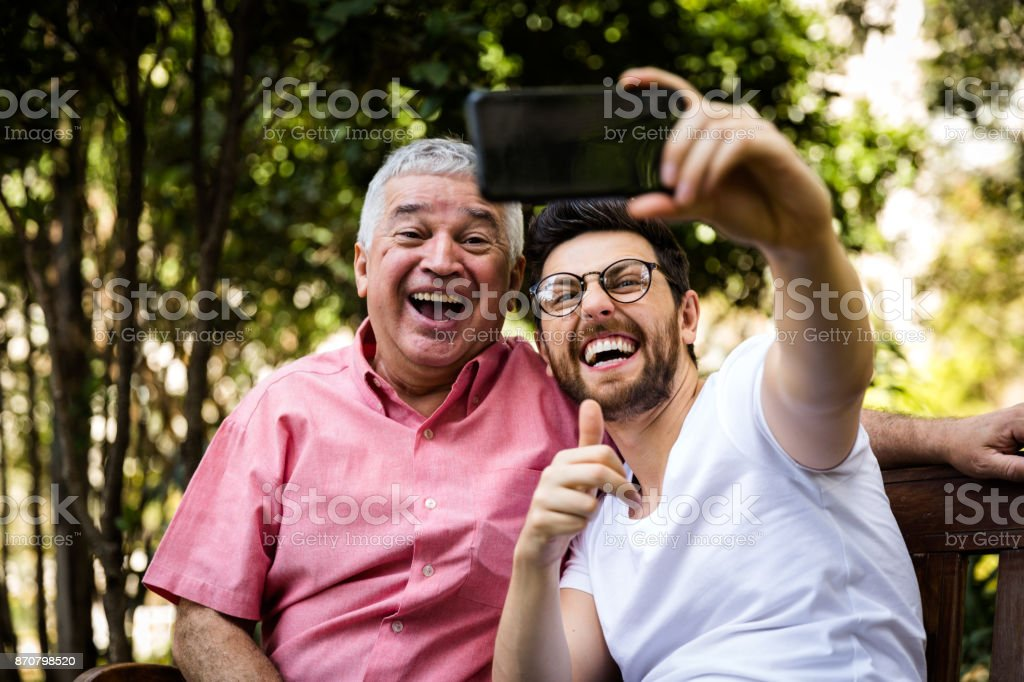 Dad and son taking selfie and having fun in the park stock photo