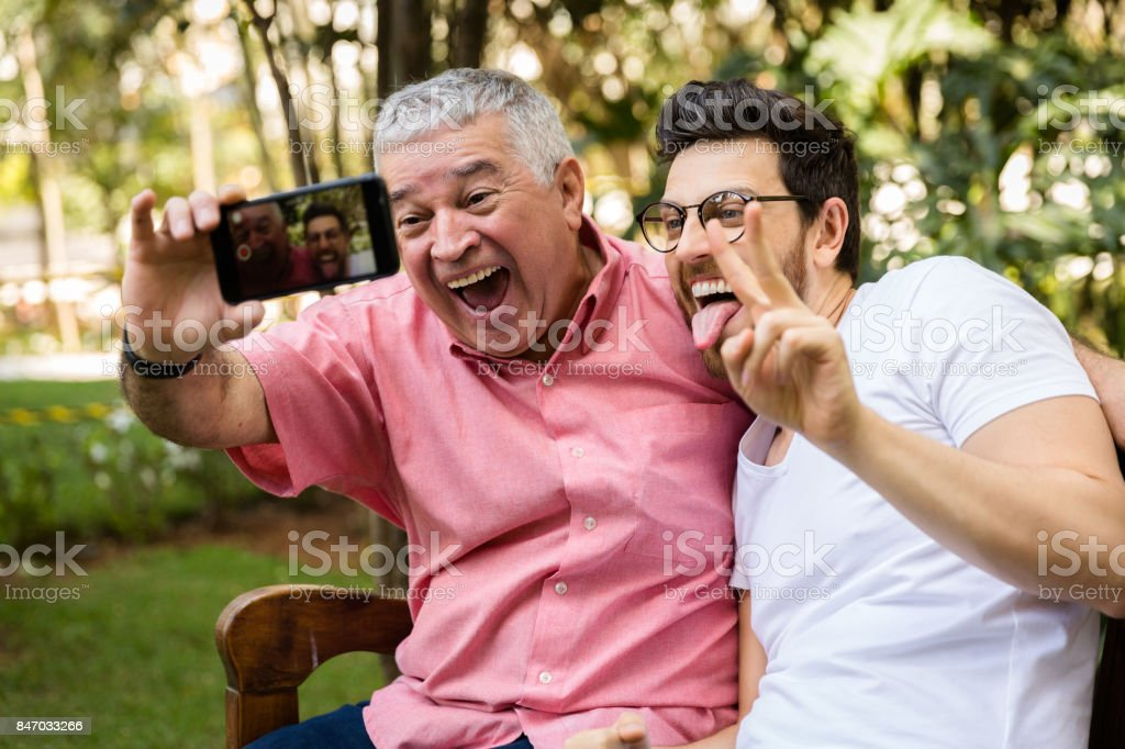 Dad and son taking selfie photo and having fun in the park stock photo