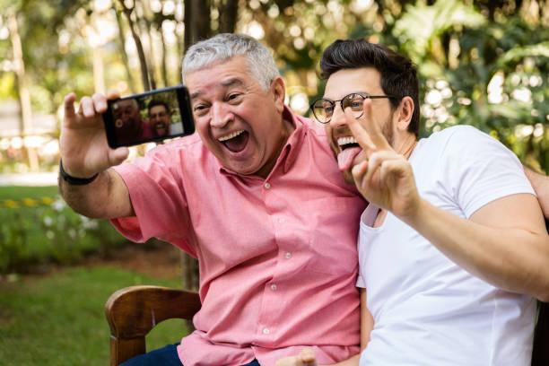 Pai e filho tirando foto de selfie e se divertindo no parque - foto de acervo