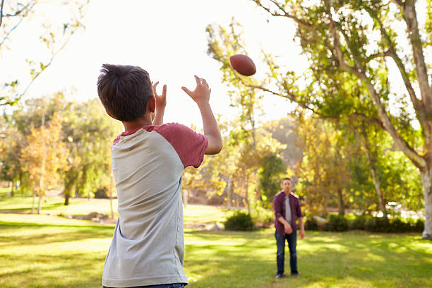 Dad and son throwing American football to each other stock photo