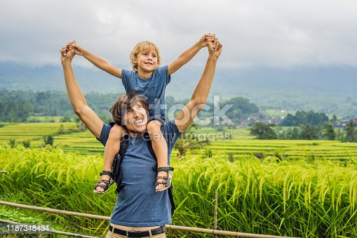 Dad and son travelers on Beautiful Jatiluwih Rice Terraces against the background of famous volcanoes in Bali, Indonesia. Traveling with children concept.