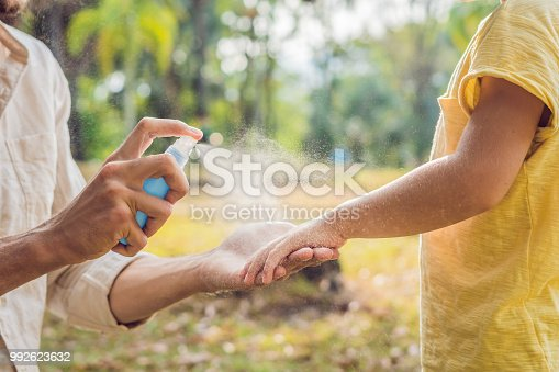 istock dad and son use mosquito spray.Spraying insect repellent on skin outdoor 992623632