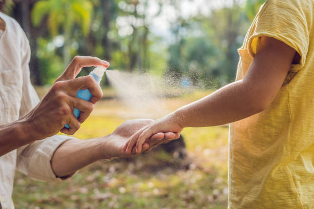 dad and son use mosquito spray.spraying insect repellent on skin outdoor - insect stock pictures, royalty-free photos & images