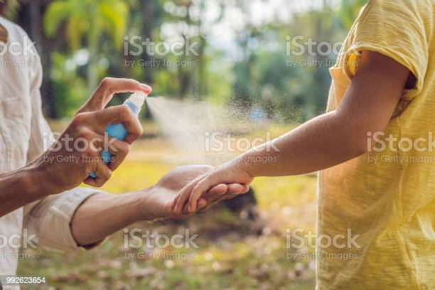 Photo of dad and son use mosquito spray.Spraying insect repellent on skin outdoor