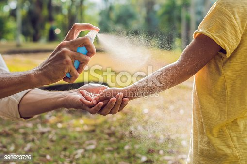 istock dad and son use mosquito spray.Spraying insect repellent on skin outdoor 992623726