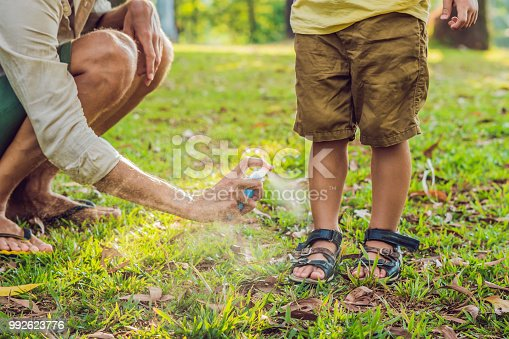 istock dad and son use mosquito spray.Spraying insect repellent on skin outdoor 992623776