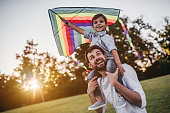 Handsome dad with his little cute sun are having fun with kite on green grassy lawn