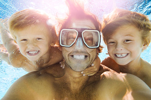 Dad and Sons Having Fun Doing A Selfie Underwater - foto stock