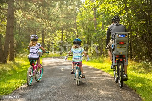 Rear view of a father and his three children (the youngest is in the seat behind him) riding bicycles on a paved path through the woods. Taken on a late summer morning in Minnesota. All four people are wearing helmets.