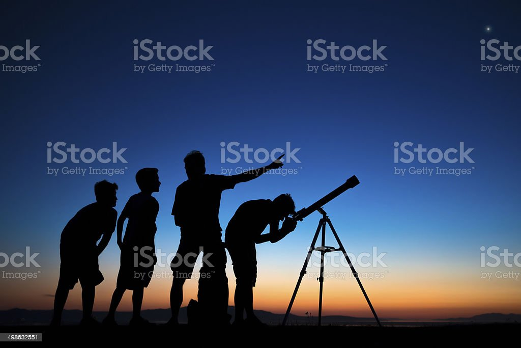 Dad and three sons looking thru a telescope stock photo