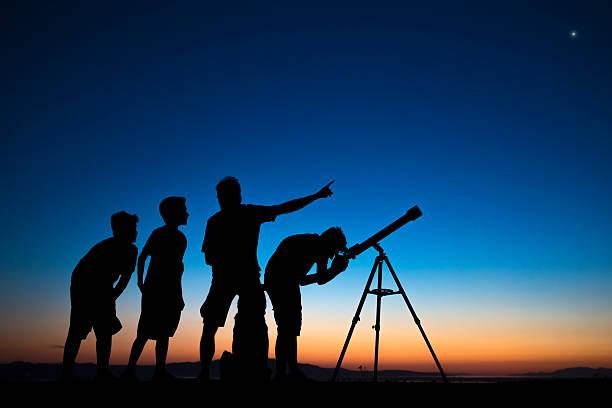 père et de trois fils à la recherche au télescope un - astronomie photos et images de collection