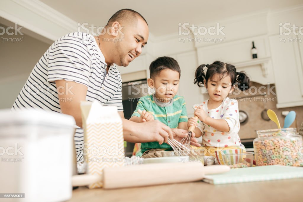 Dad baking with kids stock photo