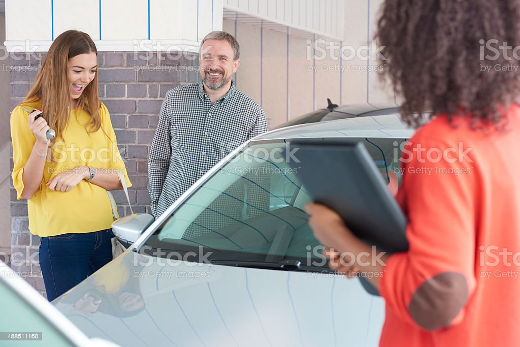 Dad buying a second hand car for his daughter stock photo