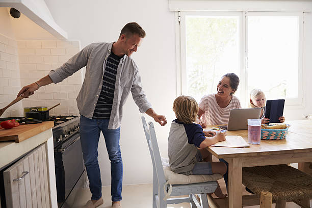 dad cooking turns to mum with kids at the kitchen - kinderküche zubehör stock-fotos und bilder