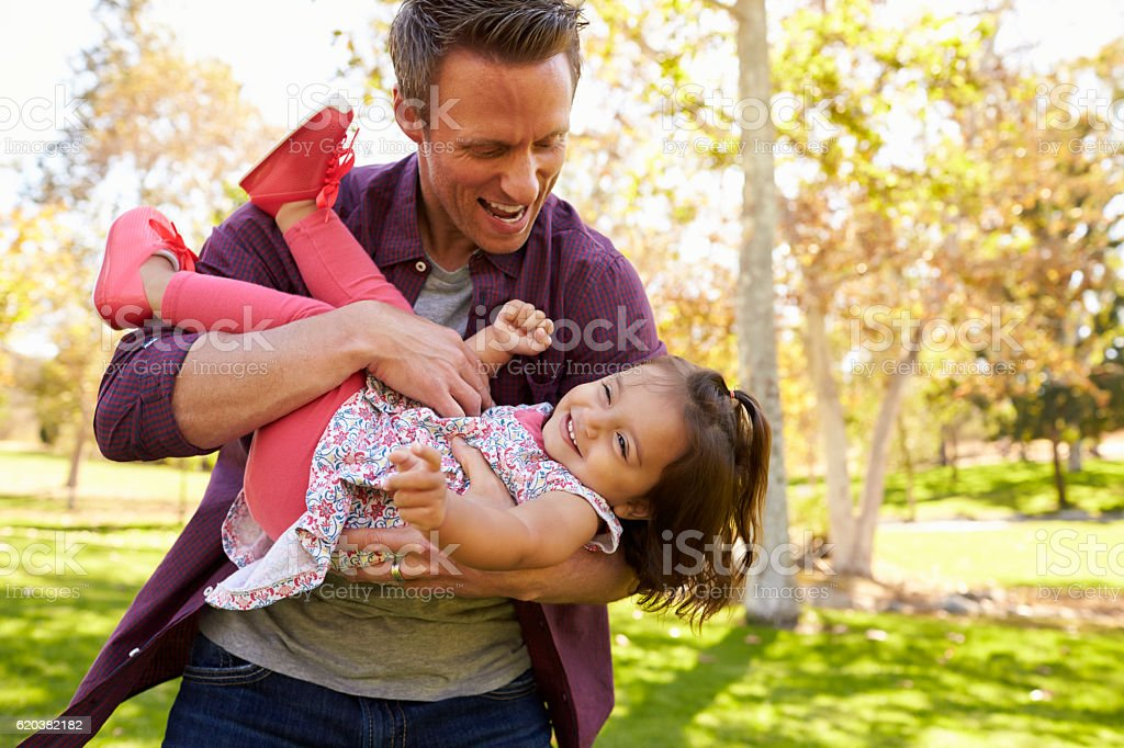 Dad cradling toddler daughter in his arms at the park stock photo