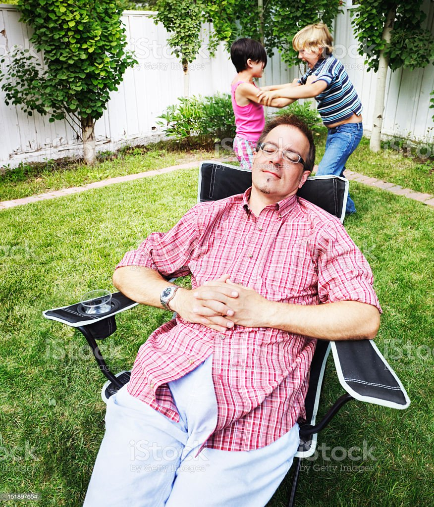Dad dozes while kids fight stock photo