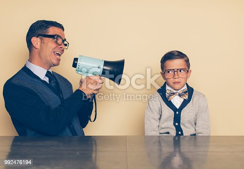 A retro dad dressed in a tie and eyeglasses is parenting his son through a megaphone. His son is looking at him out of the corner of his eye with a timid look on his face. The dad is trying to encourage his son, but the boy is unsure.