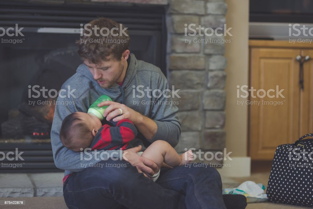 Dad feeds bottle to his young son stock photo