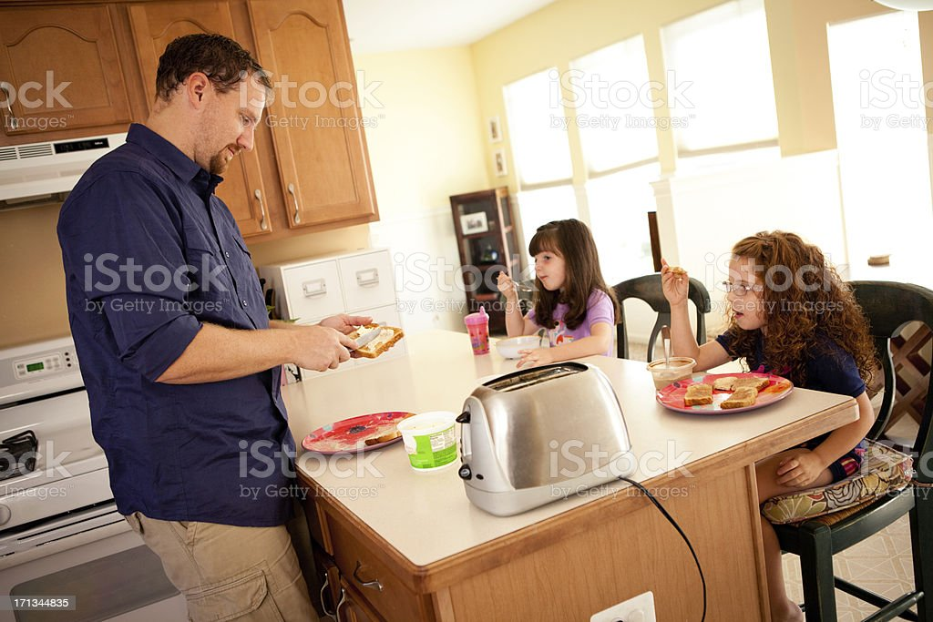 Dad Fixing Breakfast for His Little Daughters in Kitchen stock photo