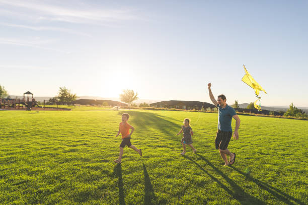 Dad flying kites with his kids at the park stock photo