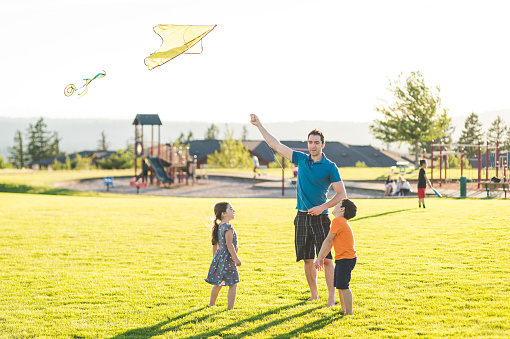 Dad Flying Kites With His Kids At The Park Stock Photo - Download Image Now  - iStock